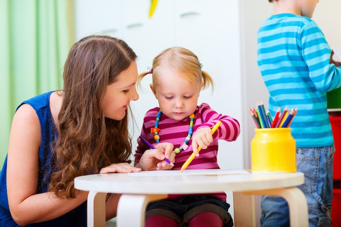 little girl coloring with daycare provider