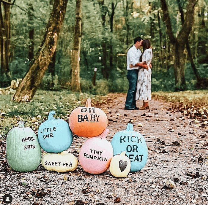 colorful pumpkins with a couple in the background announcing their pregnancy