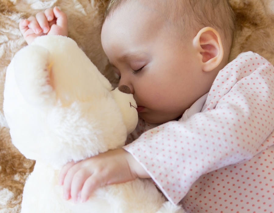 baby sleeping with stuffed animal