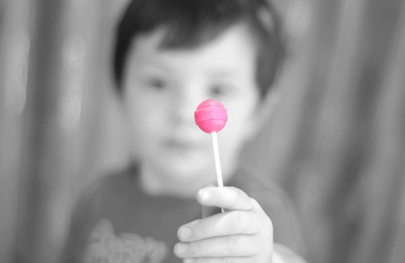 little boy eating lollipop to find out if he's having a sister or brother