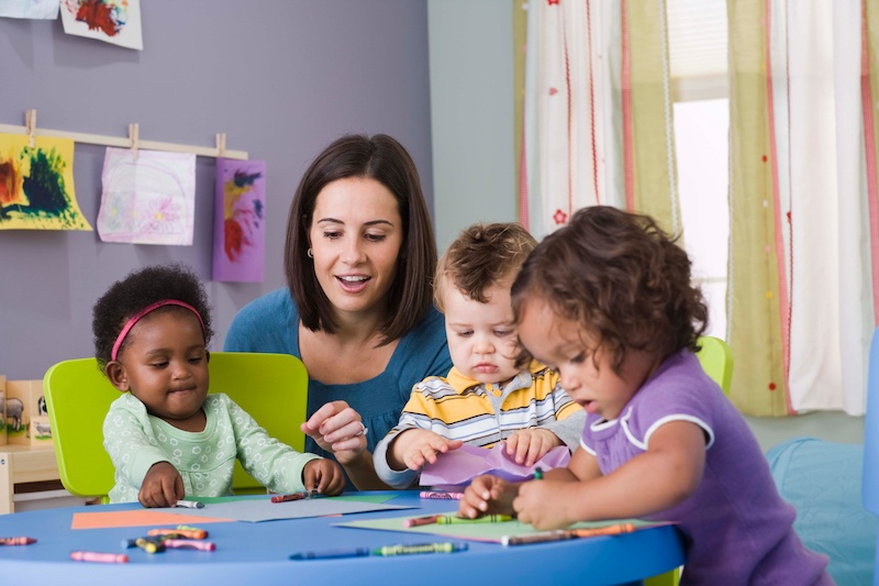 Toddlers playing with teacher at day care