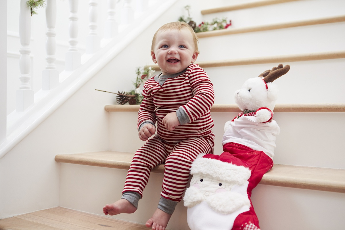 baby with stocking on stairs