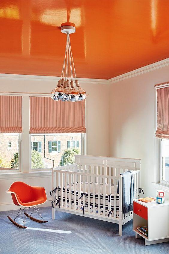 bright orange painted ceiling in baby nursery makes small room look bigger