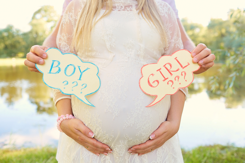 parents predicting baby's gender holding boy or girl sgns
