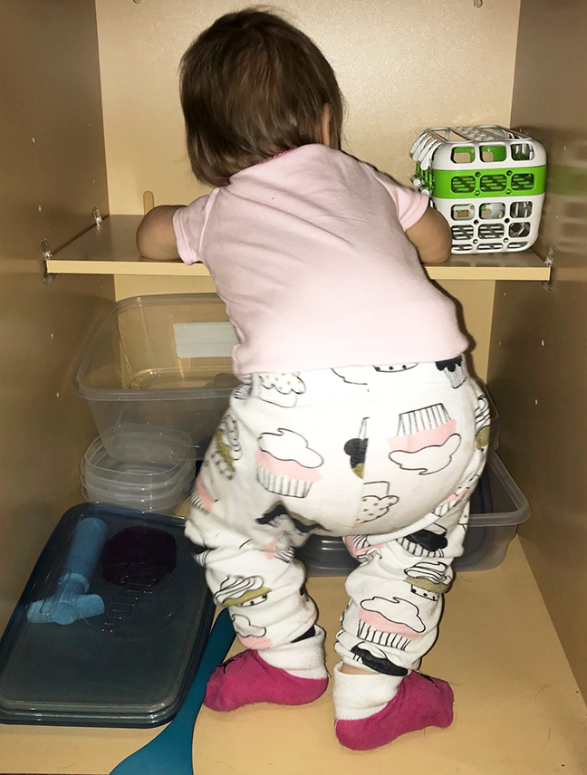 baby in tupperware cupboard
