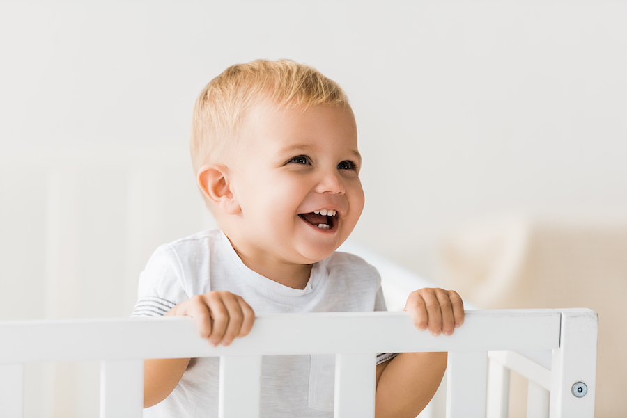 18 month old toddler happy in his crib