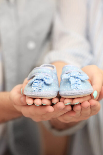 man and woman holding baby shoes to announce pregnancy