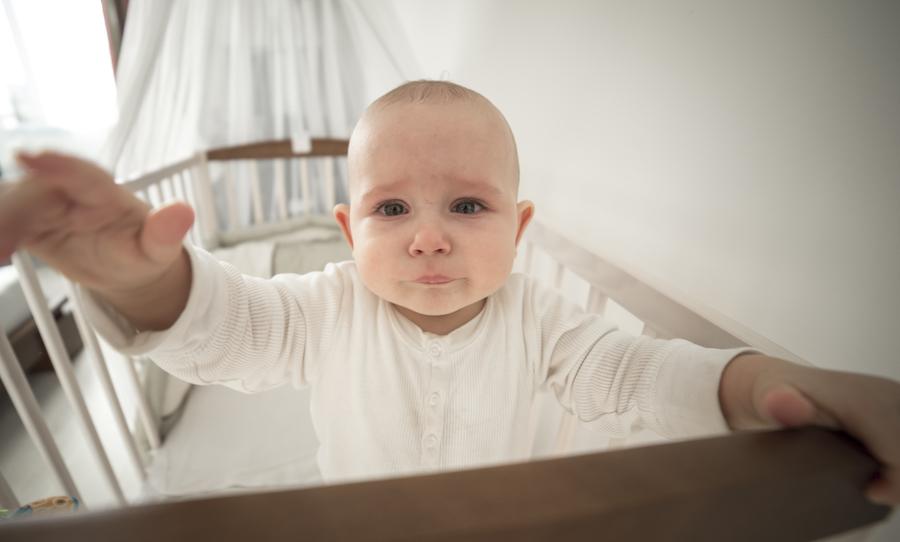 Baby standing in crib upset during sleep training