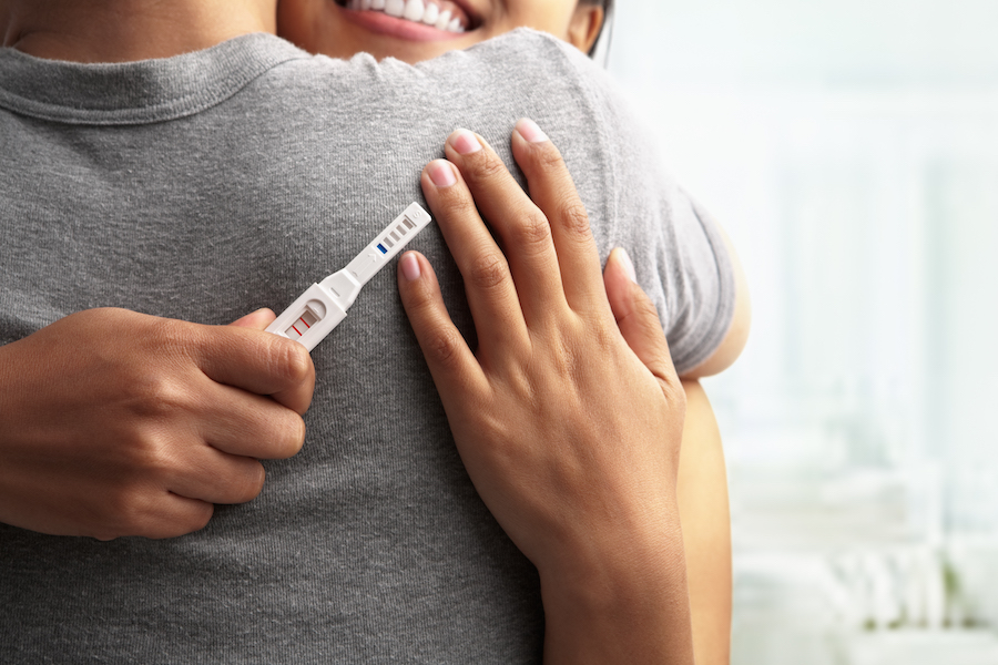 woman hugging man with positive pregnancy test on his back - what to do when you find out you're pregnant