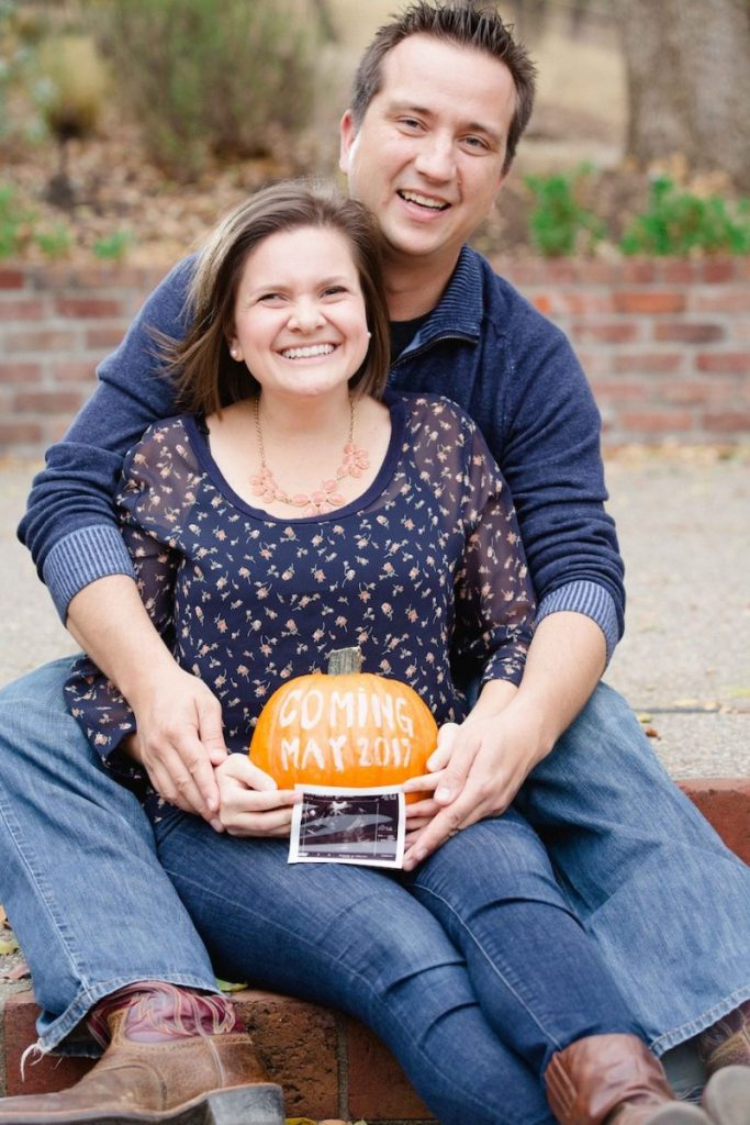 couple announcing pregnancy with a pumpkin pregnancy announcement