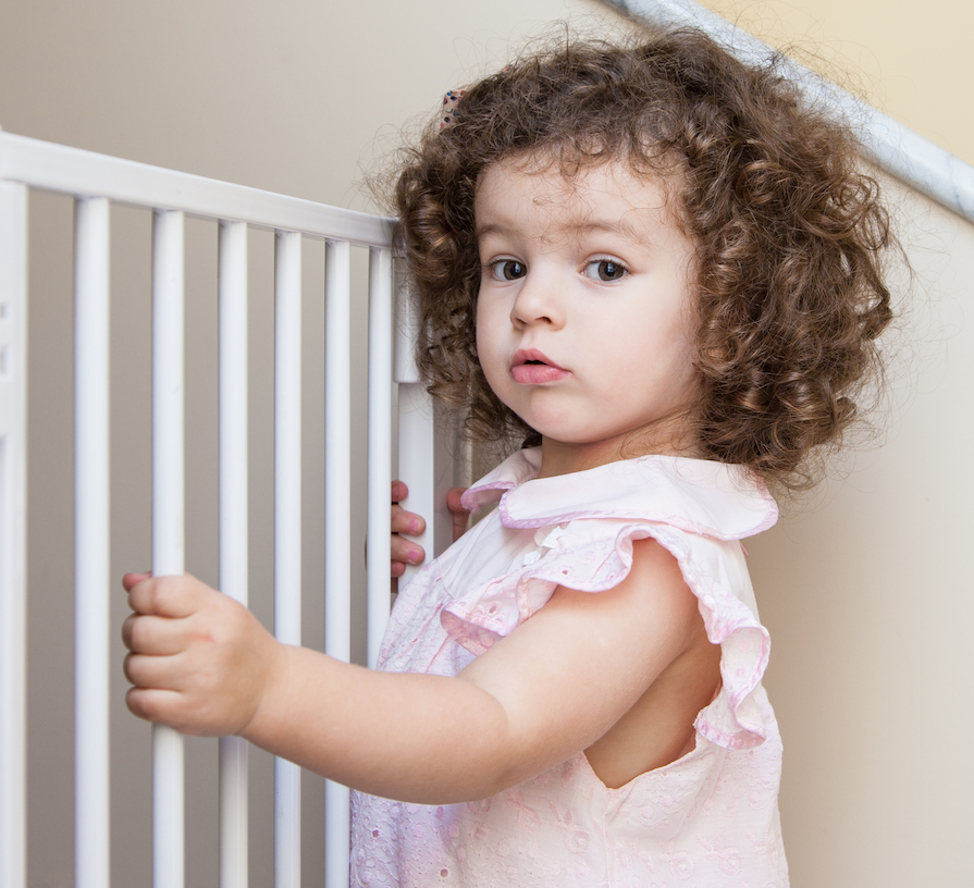 toddler sitting at baby gate when transitioning to toddler bed