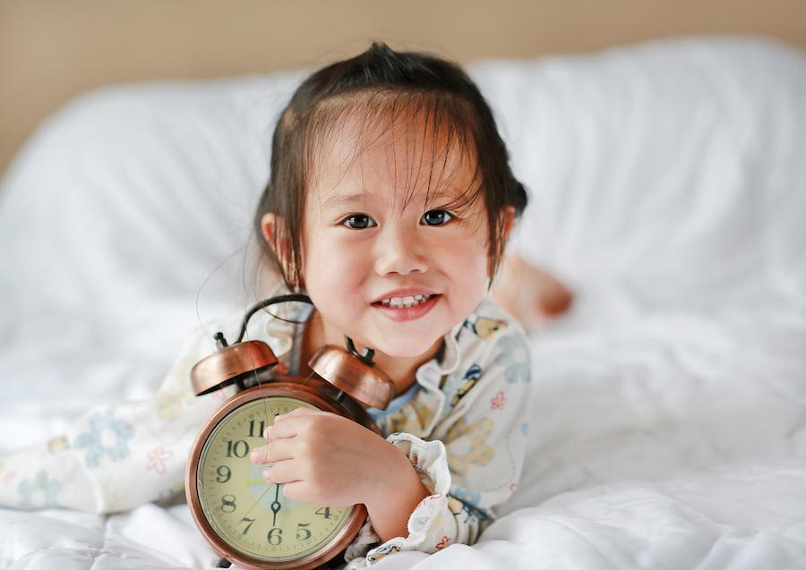 toddler girl holding alarm clock in bed