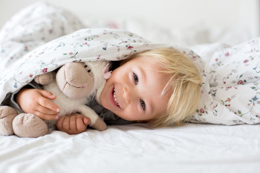 toddler boy sleeping in big bed