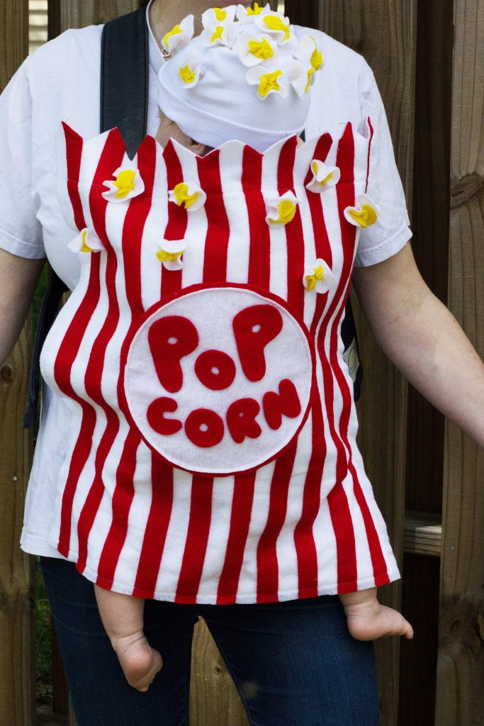 baby in a carrier dressed as popcorn halloween costume