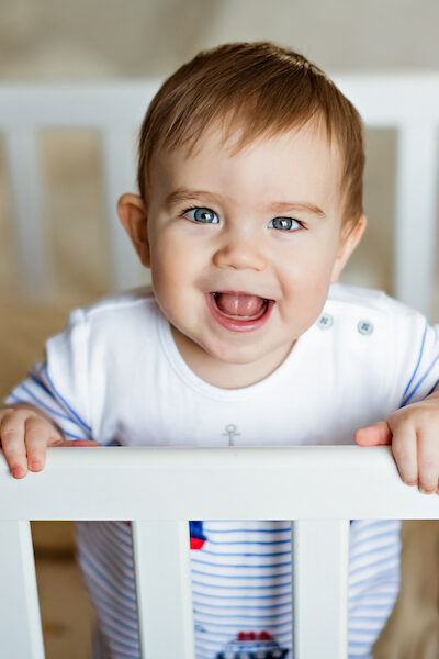 baby standing in crib happily