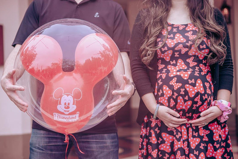 Disney pregnancy announcement - man holding Mickey Mouse balloon and woman holding pregnant belly