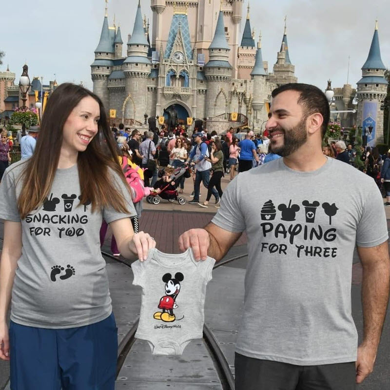 Disney pregnancy announcement - couple holding Mickey Mouse onesie at Disney