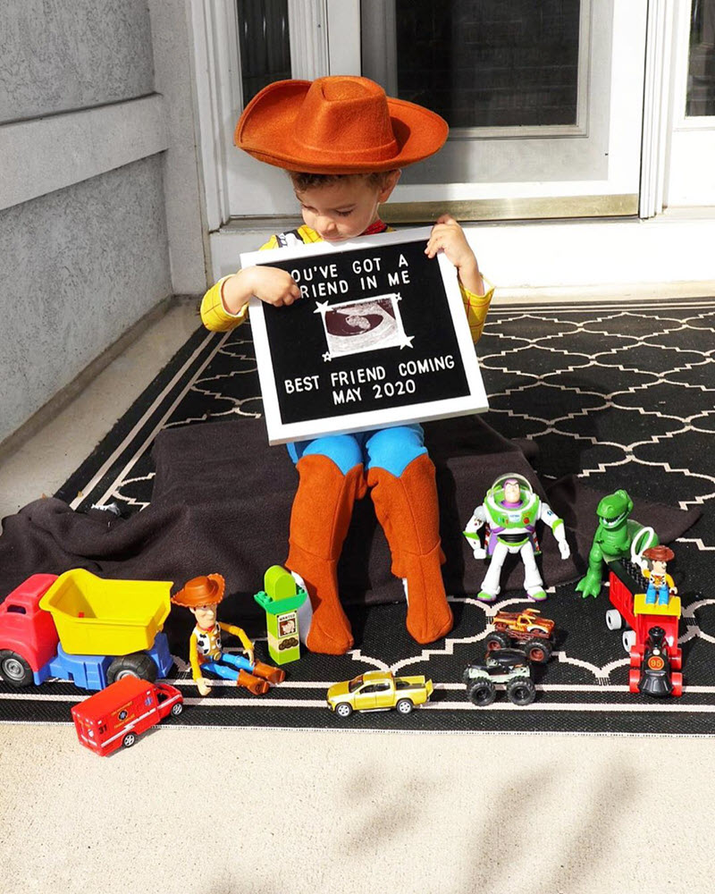 Disney pregnancy announcement - Boy dressed as Woody with Tiy Story friends surrounding him and pregnancy announcement on letter board