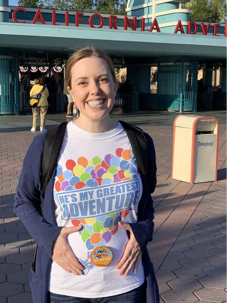 Disney pregnancy announcement - woman holding belly with Disney Up themed shirt