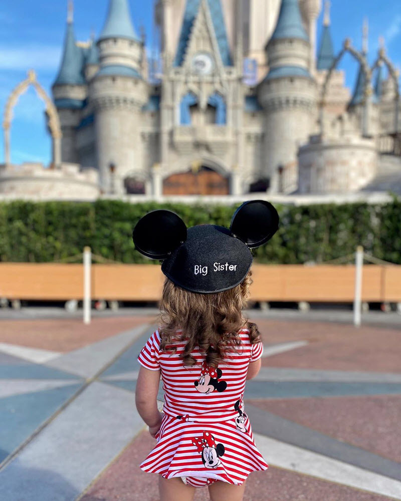 little girl wearing a Big Sister hat at Disneyland to announce pregnancy