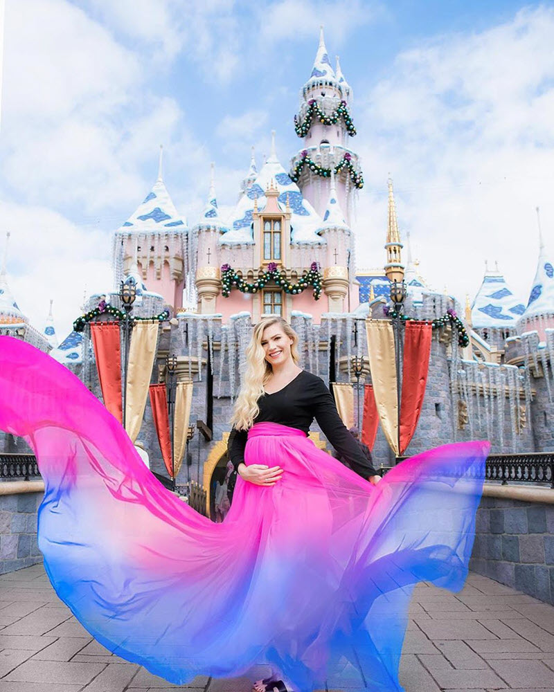 pregnant woman with cololrful skirt in front of Disney castle