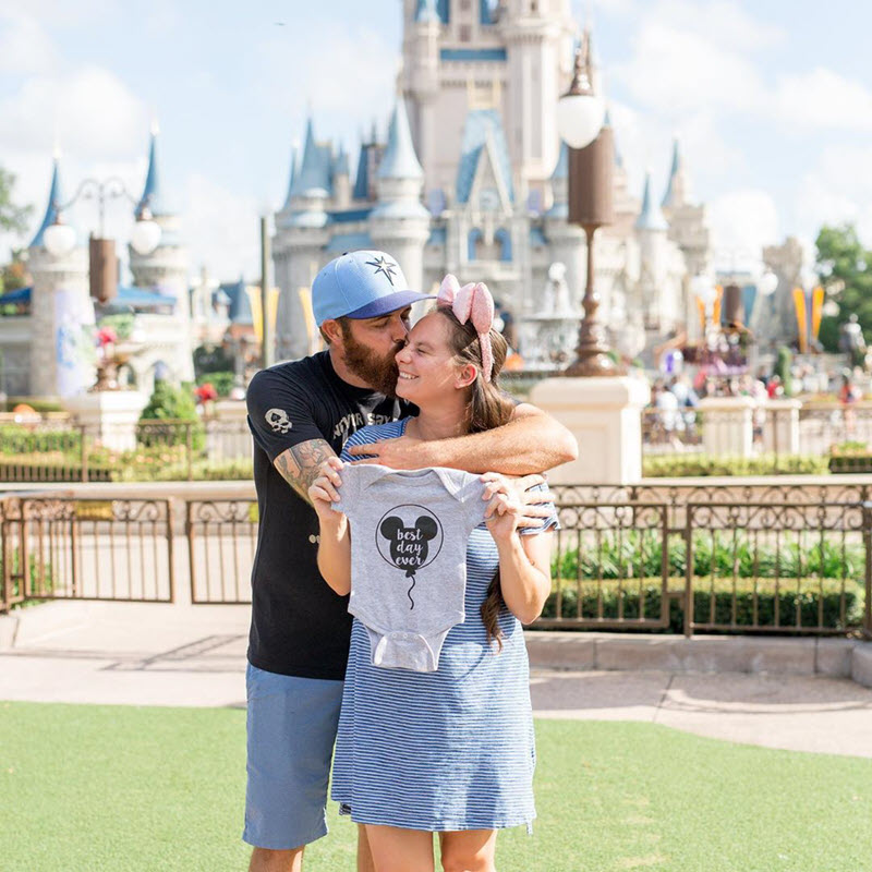 Disney pregnancy announcement - man kissing woman holding a Mickey Mouse baby onesie in front of the Sleeping Beauty castle
