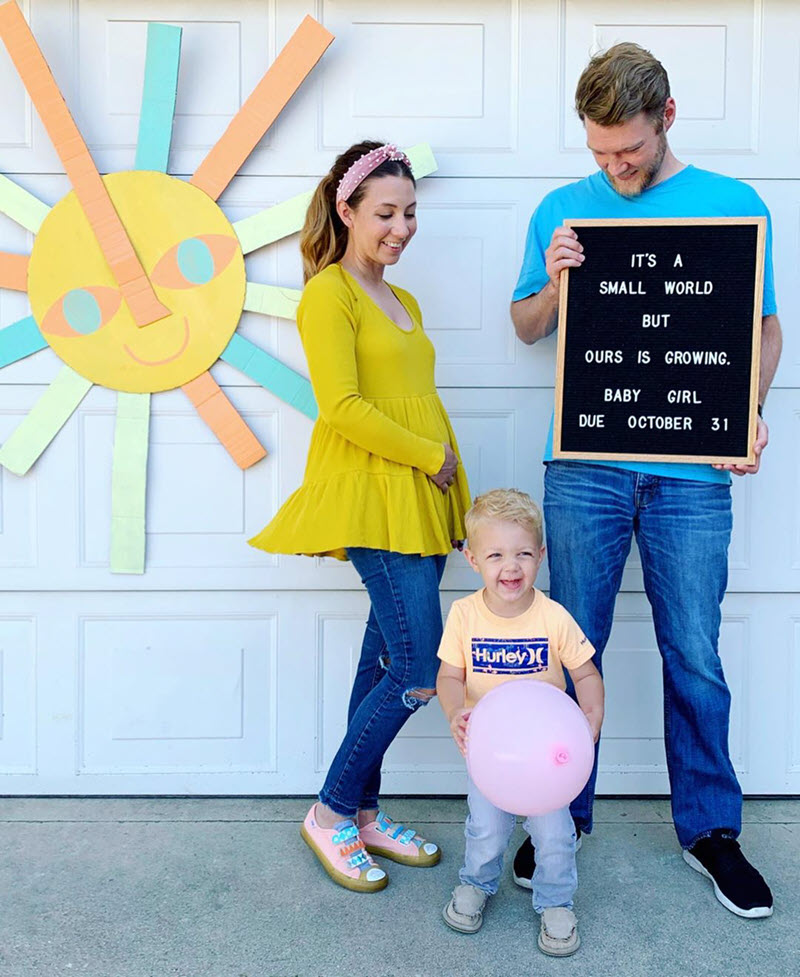 Disney pregnancy announcement - mom, dad, and brother holding a letterboard to announce pregnancy