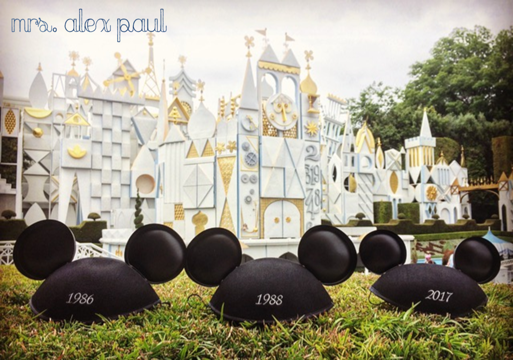 Disney pregnancy announcement - three mickey ears with parents and new baby's birth years in front of Small World ride