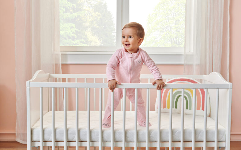 baby girl climbing out of crib
