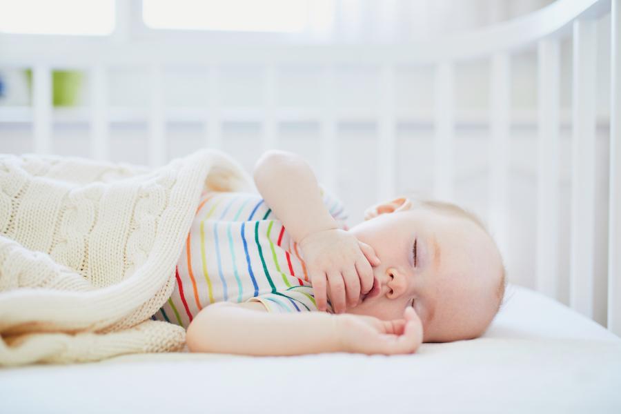 baby asleep in his crib after watching baby sleep cues