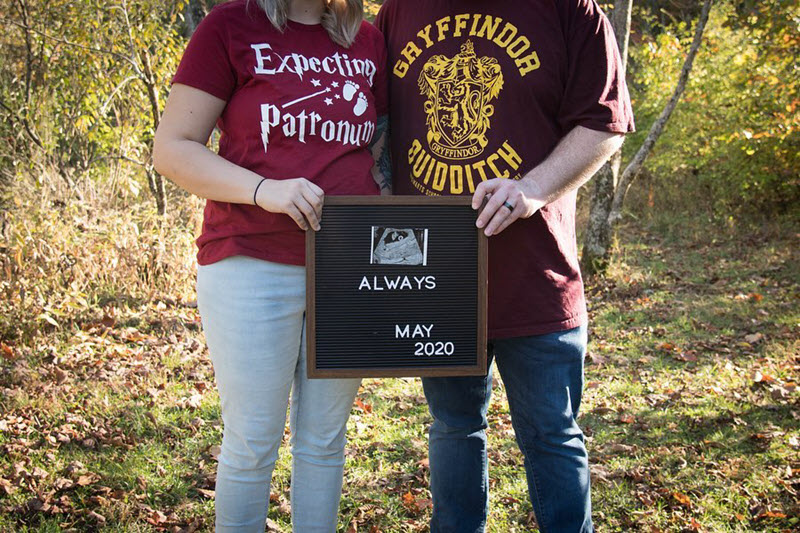 Expectant parents holding Harry Potter Always sign to announce pregnancy