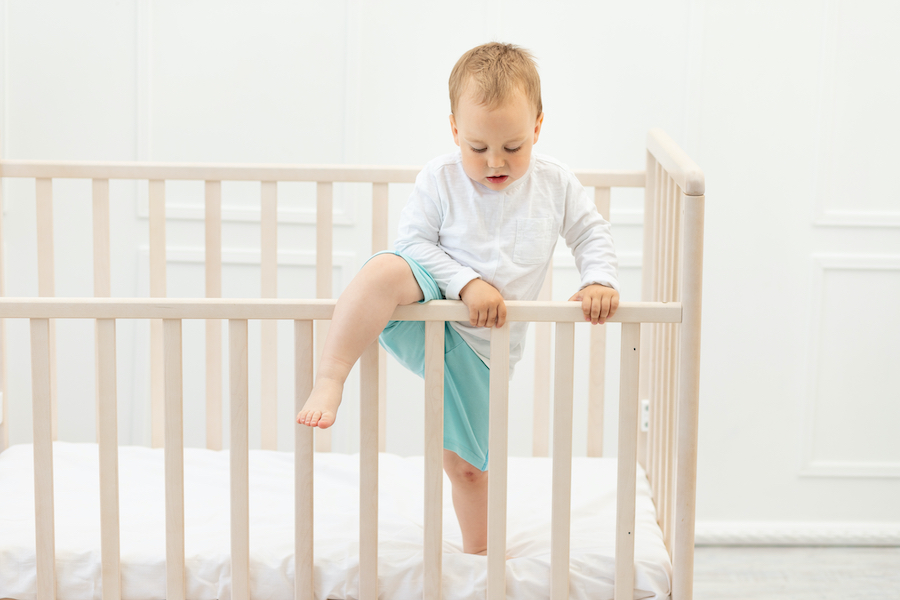 toddler boy climbing out of his crib