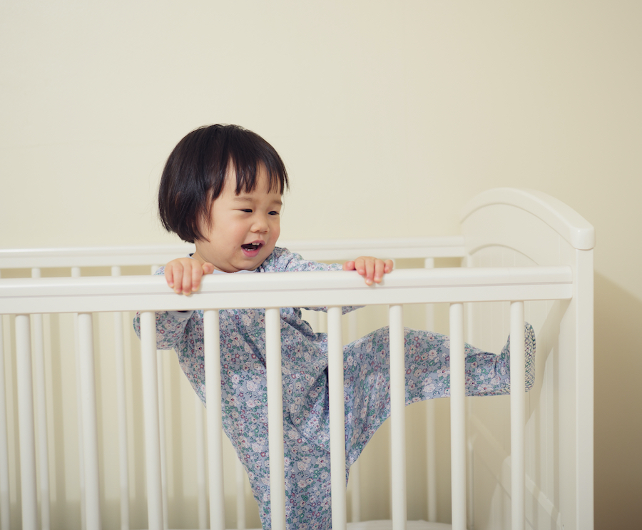 young toddler girl trying to climb out of crib