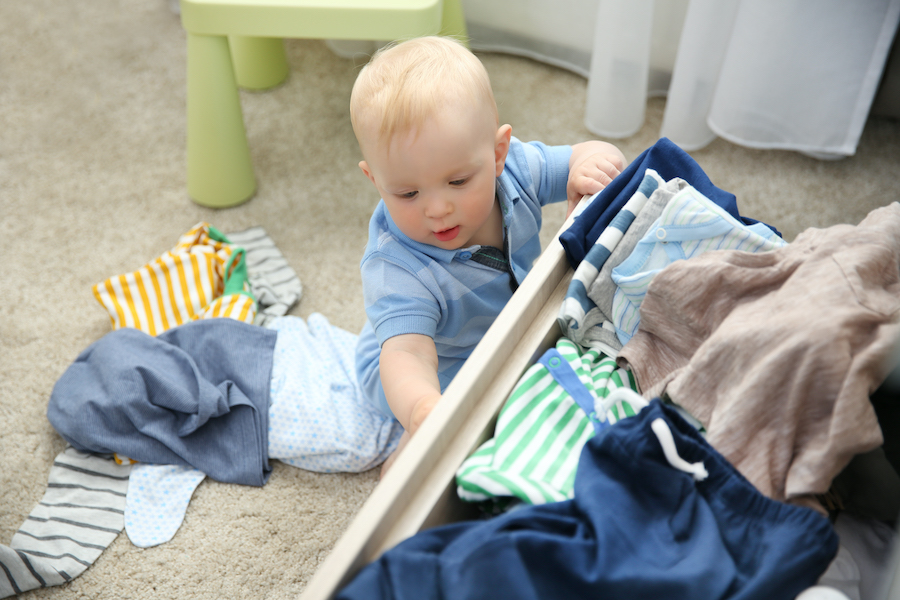 baby boy taking out clothes from dresser - how to organize baby clothes