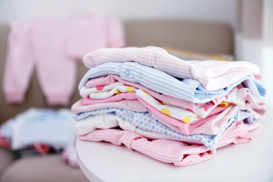 organizing baby clothes into piles