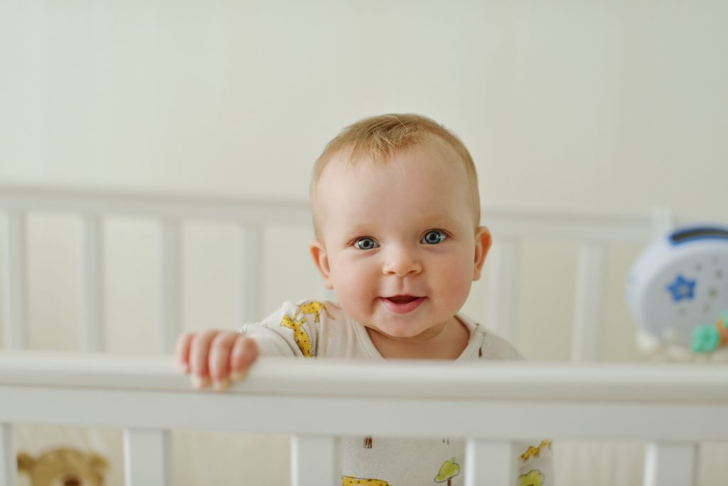 baby standing in crib smiling