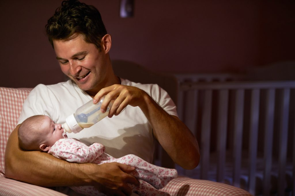dad feeding baby at night with bottle