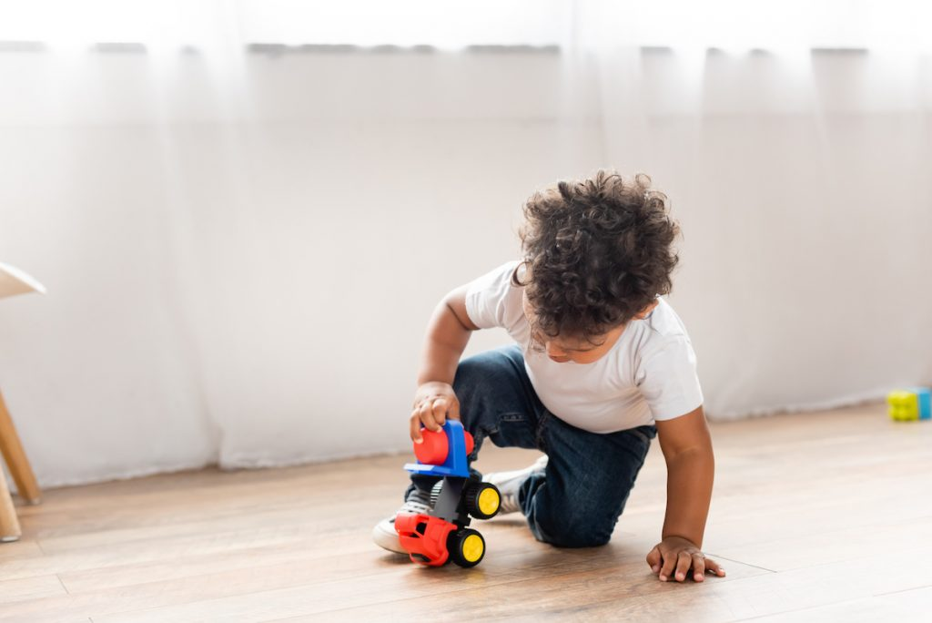 toddler playing independently with a car