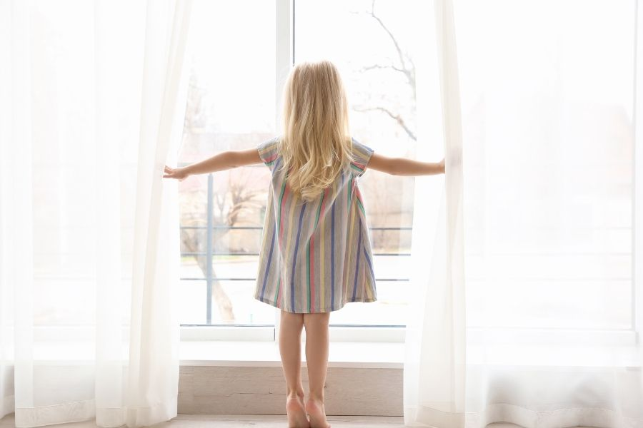 girl in nursery holding curtains back