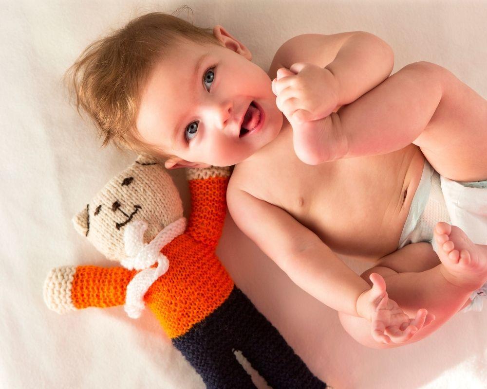 baby happily awake holding toes