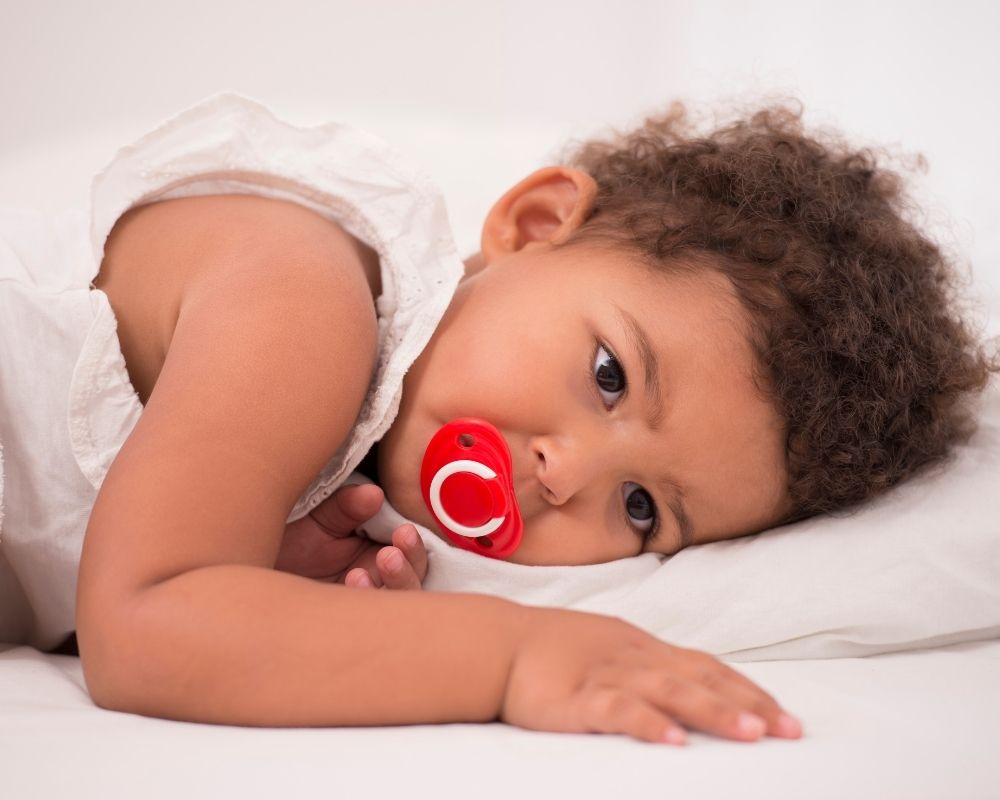 toddler lying down with pacifier