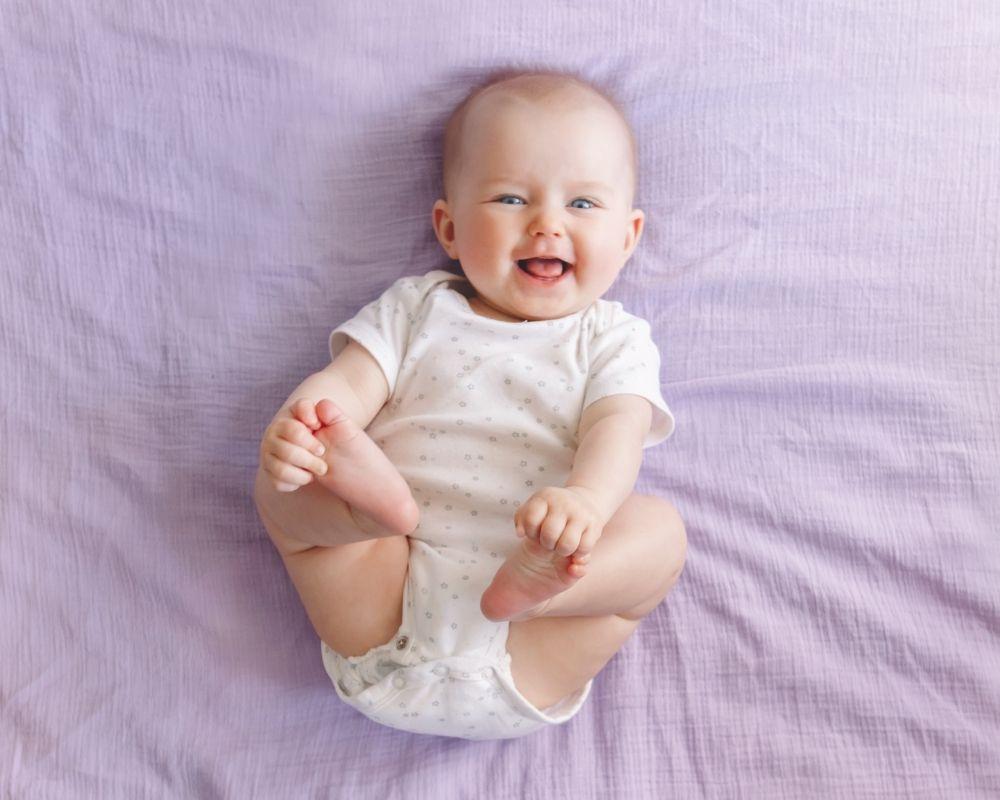 happy baby grabbing toes