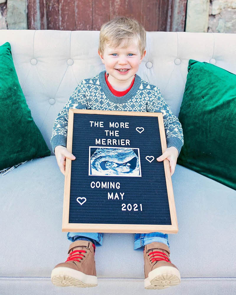 boy sitting on couch to announce new baby in family