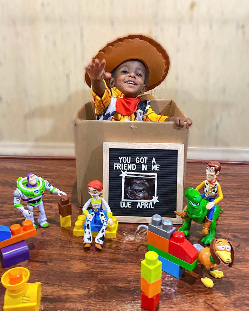 little boy dressed as Woody from Toy Story announcing new baby