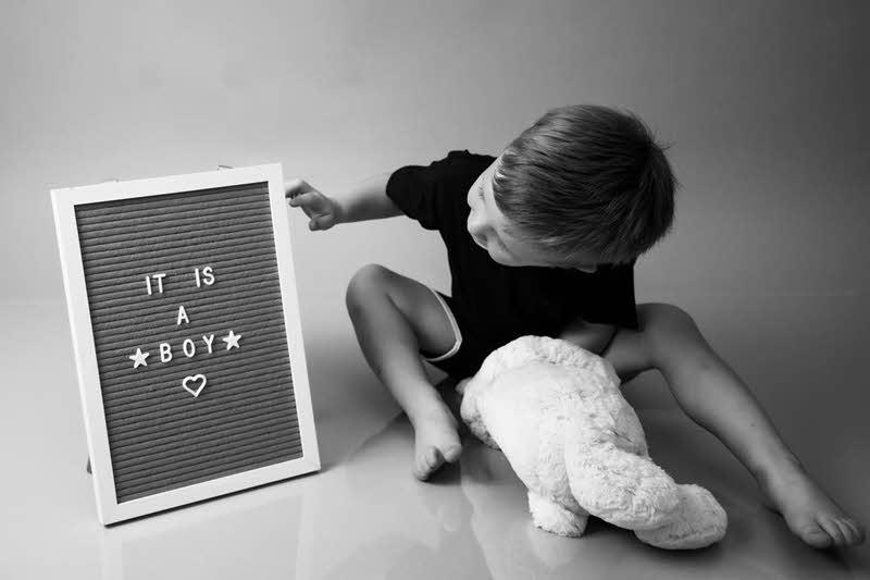 little boy looking at gender reveal letter board sign