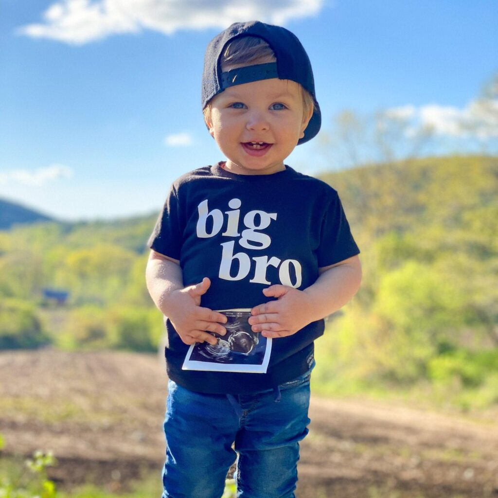 baby boy holding ultrasound photo to announce he's a big bro