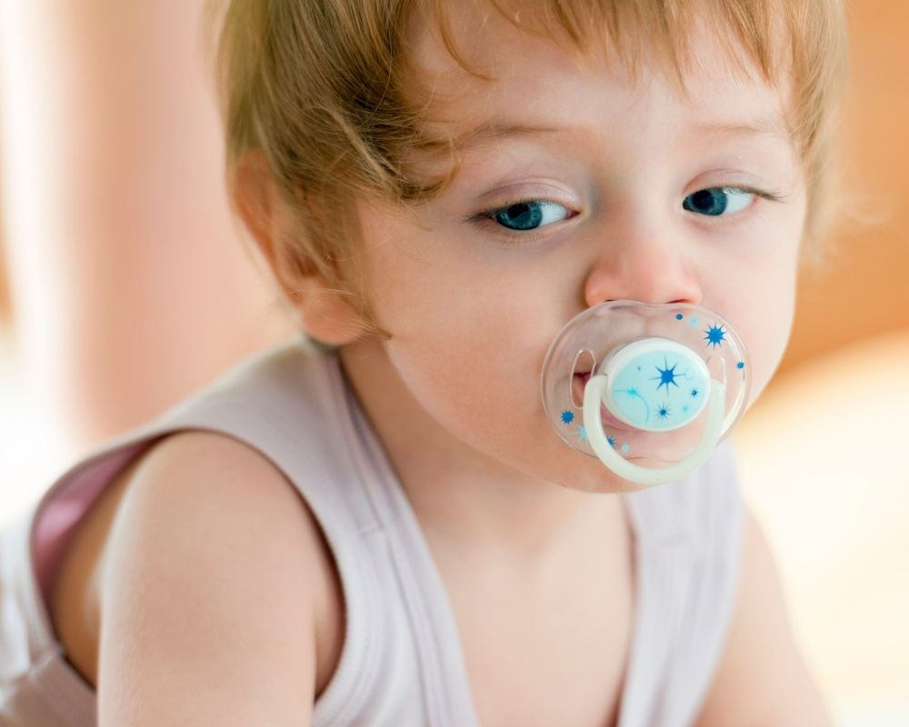 toddler with pacifier in mouth