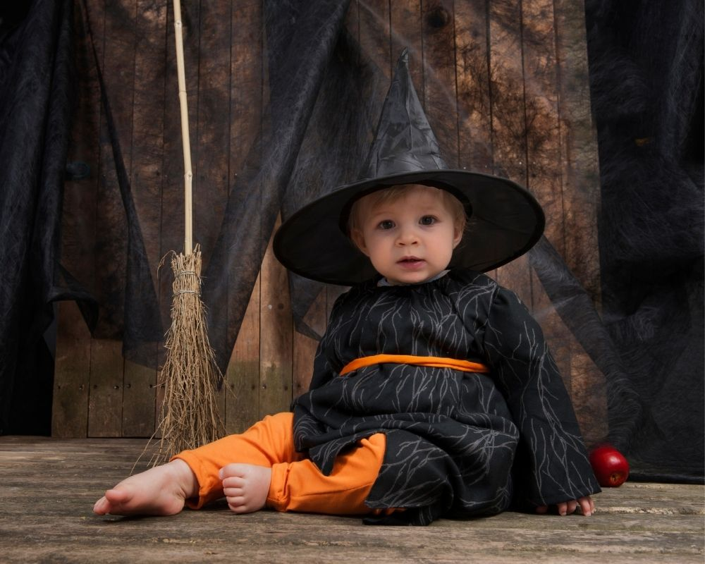 baby dressed in witch costume