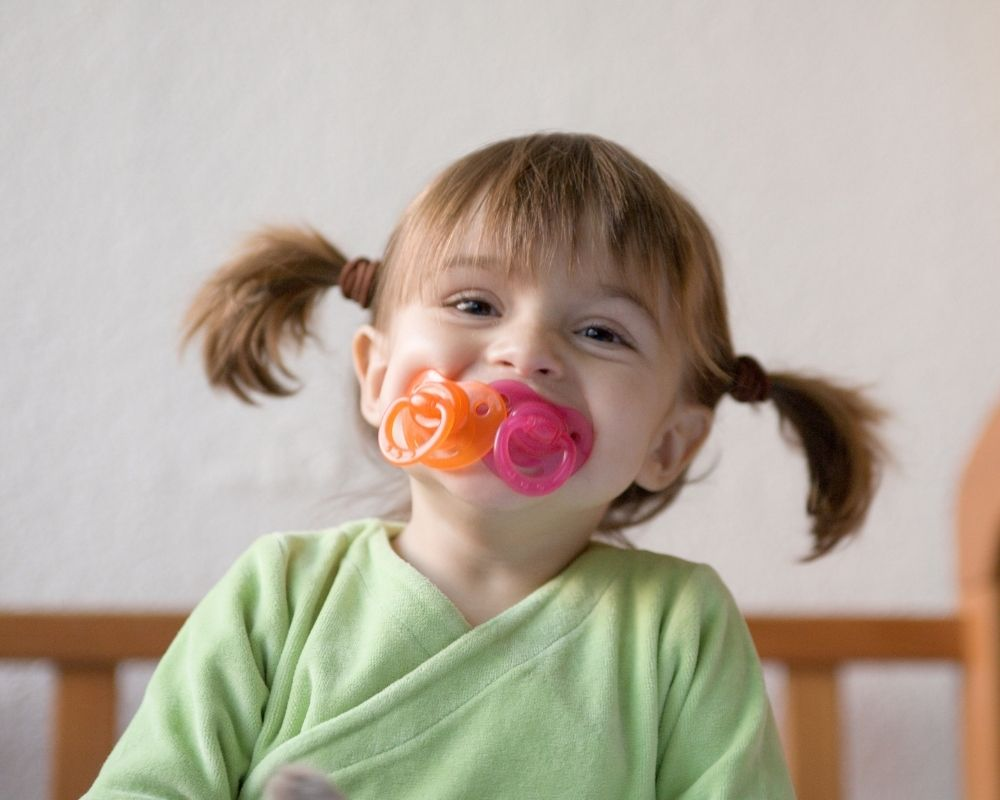 toddler with multiple pacifiers in her mouth