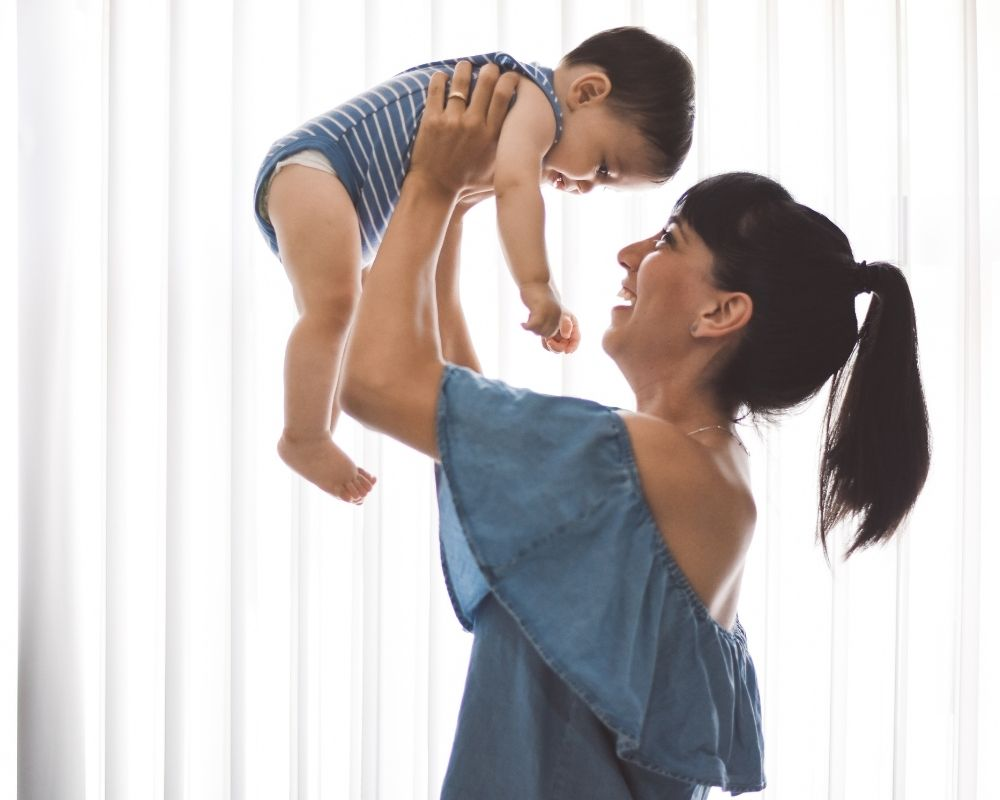 mom lifting baby in the air